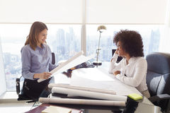 Многонациональные женщины архитектора команды с планами и проектом Стоковые Фото