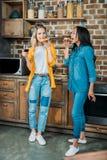 Многонациональные женщины есть пиццу и выпивая вино в кухне дома Стоковые Изображения
