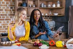Многонациональные женщины используя цифровую таблетку пока варящ совместно в кухне Стоковое Изображение