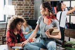 Многонациональные женщины работая пока сидящ на таблице в домашнем офисе Стоковые Фото