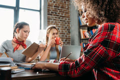 Многонациональные женщины работая пока сидящ на таблице в домашнем офисе Стоковые Изображения RF