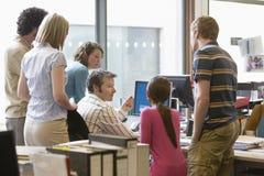 Многонациональные исполнительные власти вокруг коллеги используя компьютер Стоковая Фотография