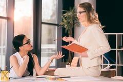 Многонациональные коммерсантки в formalwear говоря на современном офисе Стоковое Фото