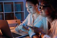 Многонациональные коммерсантки работая на компьтер-книжке пока сидящ дома офис Стоковая Фотография RF