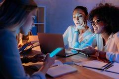 Многонациональные коммерсантки работая с цифровым офисом приборов дома Стоковая Фотография RF