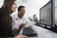 Многонациональные коллеги работая на компьютере совместно Стоковое Изображение