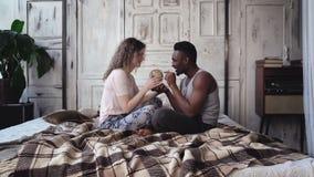 Многонациональные пары в пижамах сидя на кровати и переплетают глобус, выбирают назначение к путешествовать совместно Стоковые Изображения