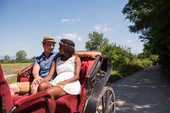 Многонациональные пары сидя в экипаже лошади стоковые фото