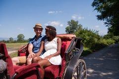 Многонациональные пары сидя в экипаже лошади стоковое фото