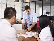 Многонациональные предприниматели обсуждая представление продаж внутри  стоковое изображение