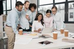 Многонациональные предприниматели работая с компьтер-книжкой совместно на офисе Стоковая Фотография