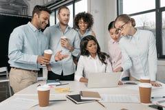 Многонациональные предприниматели работая с компьтер-книжкой совместно на офисе Стоковые Изображения