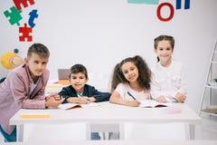 Многонациональные студенты сидя совместно на столе и усмехаясь на камере в классе Стоковые Изображения RF