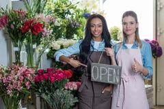Многонациональные флористы указывая на открытый знак и показывая большой палец руки вверх пока усмехающся на камере в цветочном м Стоковое Фото