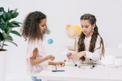 Многонациональные школьницы работая с молекулярной моделью на классе химии Стоковые Изображения