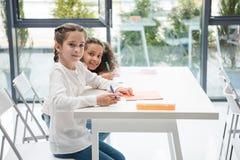 Многонациональные школьницы сидя на столе и усмехаясь на камере в классе Стоковая Фотография RF