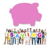 Многонациональные люди держа сбережения с копилкой Стоковое Изображение RF
