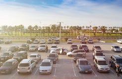 Много автомобилей припаркованы на серии открытой автостоянки, людях идут Стоковое фото RF