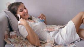 Много банкнот летают в накладные расходы воздуха в замедленном движении Девушка лежит и много падения денег на ее счастливая женщ стоковое фото