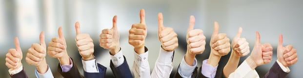 Много бизнесменов держа большие пальцы руки вверх стоковое изображение rf