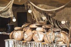 Много больших круглых ломтей хлеба лежат на durin деревянной стойки Стоковые Изображения RF