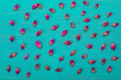 Много бутонов розы чая разбросаны на зеленое деревянное backgrou Стоковые Фото