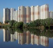 Много блока квартир над небом реки и ясности голубым Стоковая Фотография