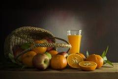 Много видов плодоовощей в a в плетеной корзине и апельсиновом соке дальше Стоковое Изображение RF