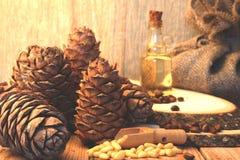 Много гайки сосны и конусы кедра рядом с бутылкой кедрового масла на таблице в деревенском стиле Стоковые Изображения