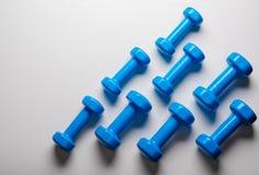 много голубых гантелей на белой предпосылке, концепции подготавливая к насмешке взгляд сверху спортивного инвентаря фитнеса вверх Стоковые Изображения RF