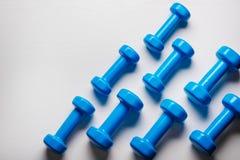 много голубых гантелей на белой предпосылке, концепции подготавливая к насмешке взгляд сверху спортивного инвентаря фитнеса вверх Стоковые Фото