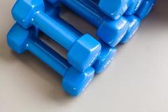 Много голубых гантелей сложили на сером поле Стоковое Фото