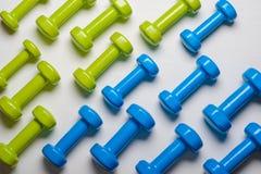 много голубых и зеленых гантелей на белой предпосылке, концепции подготавливая к насмешке взгляд сверху спортивного инвентаря фит Стоковое Изображение