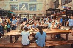 Много голодных людей есть еды вокруг таблиц внешних Стоковое фото RF