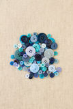 Куча голубых кнопок на hessian Стоковое фото RF