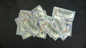 Много деньги появляются на таблицу с движением руки Кренить на черной предпосылке сток-видео