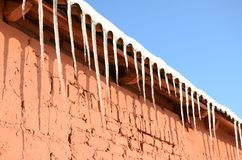 Много длинные сосульки висят под крышей красного кирпичного здания Стоковая Фотография