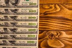 Много 100 долларовых банкнот на деревянном столе Стоковое Изображение