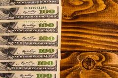Много 100 долларовых банкнот на деревянном столе Стоковая Фотография