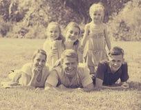 Многодетная семья лежа на траве в парке Стоковые Фотографии RF