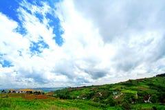 Много загородных домов на холме высоких гор с красивым голубым небом Стоковая Фотография RF