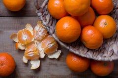 Много зрелых мандаринов в корзине Одно слезло и разделило в дольки Стоковая Фотография