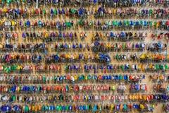Много ключи с красочными пластиковыми ключевыми бирками вися на крюках на деревянной доске стоковое изображение