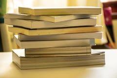 Много книг штабелированных на его столе стоковое изображение rf