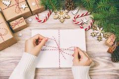 Много конвертов связанных с веревочкой Взгляд сверху конца-вверх рук famale с конвертом Конусы сосны и украшение рождества на ста стоковые фото