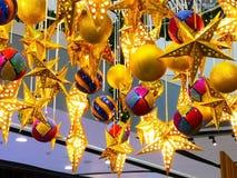 Много красивых золотых звезд с электрической лампочкой внутри и много colo Стоковые Фотографии RF