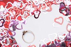 Много красная форма сердца на белой предпосылке, обручальном кольце с диамантом, рамке и космосе для текста Стоковое Фото