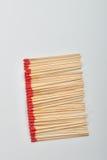 Много красных головных спичек положили прямо в линию на белую предпосылку Стоковая Фотография