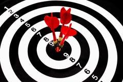 Много красных стрелок дротика ударяя в центре цели dartboard Стоковые Изображения RF