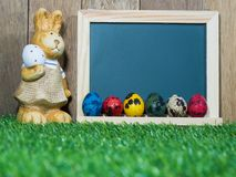 Много красочные пасхальных яя помещенных перед классн классным с кроликом пасхи Классн классный с красочным пасхальных яя и пасхи Стоковая Фотография